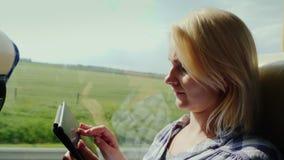 Взгляд со стороны: Молодая женщина путешествует шиной, наслаждается таблеткой Вне окна живописный район, шина быстро акции видеоматериалы