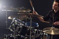 Взгляд со стороны молодого барабанщика играя набор барабанчика в студии Стоковые Фото