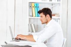 Взгляд со стороны молодого бизнесмена в рубашке работая с компьтер-книжкой Стоковые Фото