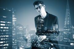 Взгляд со стороны молодого бизнесмена используя компьтер-книжку на абстрактной предпосылке города Стоковая Фотография RF