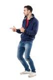 Взгляд со стороны молодого вскользь парня указывая палец показывая жест рукой пистолета Стоковая Фотография