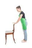 Взгляд со стороны молодого работника держа деревянный стул Стоковые Фото