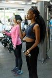 Взгляд со стороны молодого черного Афроамериканца и азиатские сексуальные женщины делая тренировку фитнеса работают с гантелями с Стоковые Изображения