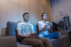 Взгляд со стороны молодого человека и женщины играя видеоигры Стоковые Фотографии RF