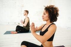 Взгляд со стороны молодой африканской женщины делая йогу Стоковое фото RF
