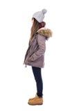 Взгляд со стороны молодой женщины в одеждах зимы изолированных на белизне Стоковые Изображения RF