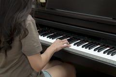 Взгляд со стороны молодой женщины играя рояль Стоковая Фотография RF