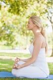Взгляд со стороны молодой женщины размышляя сидя на циновке тренировки Стоковые Изображения RF