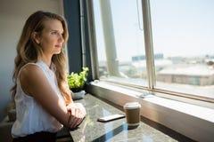 Взгляд со стороны молодой коммерсантки смотря через окно Стоковая Фотография