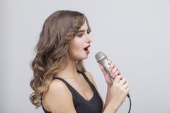 Взгляд со стороны молодой красивой девушки с микрофоном Стоковая Фотография RF