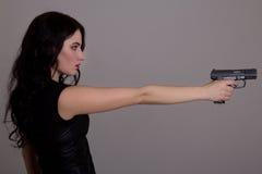 Взгляд со стороны молодой красивой женщины с оружием над серым цветом Стоковая Фотография