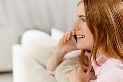 Взгляд со стороны молодой привлекательной женщины имея телефонный разговор Стоковые Фото