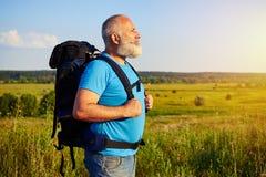 Взгляд со стороны постаретого человека нося рюкзак против backgrou поля Стоковые Изображения