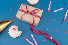 Взгляд со стороны подарочной коробки, тортов и свечей на сини Стоковая Фотография RF
