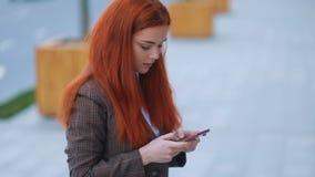 Взгляд со стороны рыжеволосой изумительной модельной девушки businness с нежными руками в коричневой куртке и белой футболке испо акции видеоматериалы