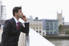 Взгляд со стороны серьезного индийского бизнесмена на звонке outdoors Стоковое фото RF