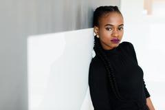 Взгляд со стороны серьезной африканской или черной американской женщины смотря камеру стоя над белой предпосылкой Стоковые Фото