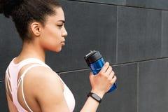 Взгляд со стороны снятый молодой спортсменки держа бутылку Стоковое Изображение RF