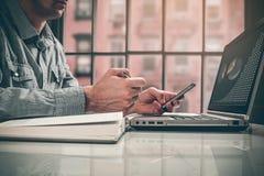 Взгляд со стороны снял рук ` s человека используя умный телефон в интерьере, вид сзади рук бизнесмена занятых использующ сотовый  Стоковая Фотография
