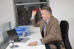 Взгляд со стороны средн-постаретого самолета бизнесмена бросая бумажного в офисе Стоковое Изображение