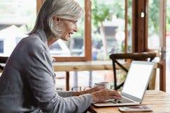 Взгляд со стороны старшей женщины используя портативный компьютер пока сидящ на таблице Стоковое Изображение
