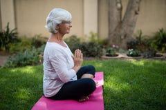 Взгляд со стороны старшей женщины размышляя в положении молитве Стоковая Фотография RF