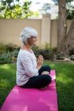 Взгляд со стороны старшей женщины размышляя на циновке тренировки Стоковые Изображения