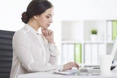 Взгляд со стороны строгой женщины работая в офисе Стоковые Фото