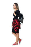 Взгляд со стороны сумки нося молодой девушки студента модной идя и смотря вверх стоковые изображения rf