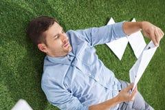 Взгляд со стороны сфокусированного бизнесмена анализируя документы Стоковые Изображения RF