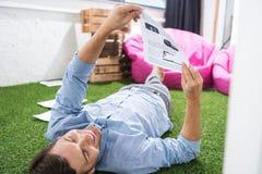 Взгляд со стороны сфокусированного бизнесмена анализируя документы Стоковое фото RF