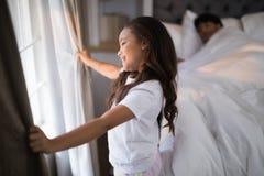 Взгляд со стороны счастливой девушки держа занавесы в спальне Стоковая Фотография RF