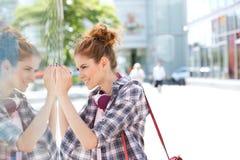 Взгляд со стороны счастливых покупок окна женщины в городе Стоковые Изображения