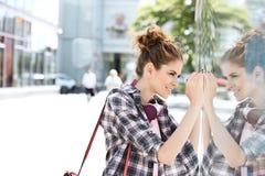 Взгляд со стороны счастливых покупок окна женщины в городе Стоковая Фотография