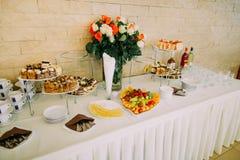 Взгляд со стороны таблицы свадьбы покрытой с плодоовощ, тортами, напитками и украшенной с розами стоковое фото rf