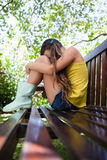 Взгляд со стороны унылой девушки сидя на деревянной скамье Стоковая Фотография RF