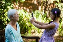 Взгляд со стороны усмехаясь девушки фотографируя бабушку Стоковое фото RF