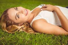 Взгляд со стороны усмехаясь женщины лежа на траве Стоковое фото RF