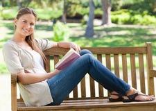 Взгляд со стороны усмехаясь женщины при ее книга сидя на парке ben Стоковая Фотография