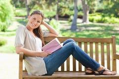 Взгляд со стороны усмехаясь женщины сидя на скамейке в парке с ее bo Стоковые Изображения RF