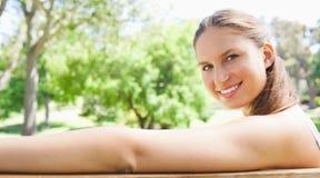 Взгляд со стороны усмехаясь женщины сидя на скамейке в парке Стоковое Изображение RF