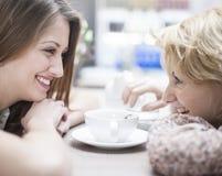 Взгляд со стороны усмехаясь молодых женских друзей смотря один другого в кафе Стоковые Фото