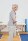Взгляд со стороны усмехаясь старшей женщины с костылями Стоковое Изображение RF