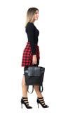 Взгляд со стороны усмехаясь сумки нося молодой стильной женщины стиля улицы идя и смотря вверх Стоковое фото RF