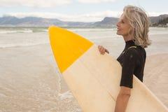 Взгляд со стороны усмехаясь surfboard нося женщины пока стоящ на береге Стоковые Фото
