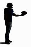 Взгляд со стороны футболиста силуэта американского держа шарик Стоковые Изображения