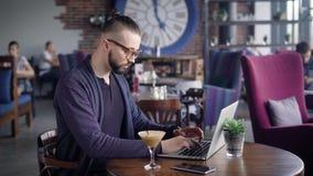 Взгляд со стороны человека в черной футболке и синем пиджаке сидя на таблице используя компьтер-книжку Молодой битник с современн сток-видео