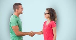 Взгляд со стороны человека и женщины тряся руки над голубой предпосылкой стоковое изображение