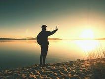 Взгляд со стороны человека принимая фото Selfie на пляж Горячее утро Солнце поднимая над озером Стоковые Изображения RF
