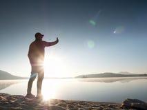 Взгляд со стороны человека принимая фото Selfie на пляж Горячее утро Солнце поднимая над озером Стоковое Изображение